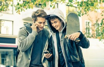 36239653 - young hipster brothers having fun with smartphone - best friends sharing free time with new trends technology - guys enjoying everyday life moments texting connected with modern smart phone device