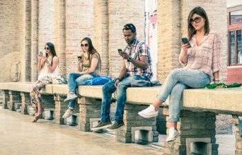 40301664 - group of young multiracial friends using smartphone with mutual disinterest towards each other  technology addiction in actual lifestyle  soft vintage filtered look with main focus on male person