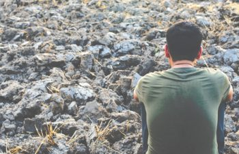 64160221 - sad young man sitting on barren ground