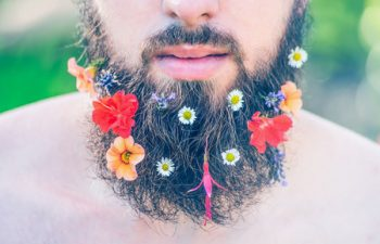 44572541 - man's face with a beard with flowers in his beard close-up on green natural background, toned