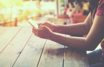 59862987 - side view of a woman using mobile smart phone in cafe sitting at wooden table outdoor area. coffee shop background. (vintage color tone)