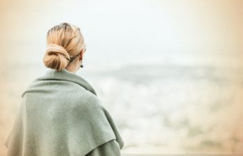 60240496 - back view of a woman with tied blond hair looking at the nature background during a nice sunny morning. photo with retro filter effect.