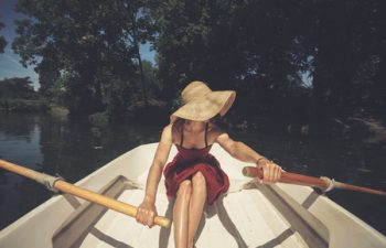 29284547 - a young woman is rowing a boat on a summer day