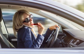 Busy woman talks on phone and does makeup while driving a car