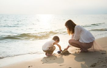 47198631 - mother and son playing on the beach,vintage filter
