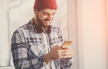 65687052 - handsome happy hipster using smart phone at window. young man wearing headphones and shuffling music