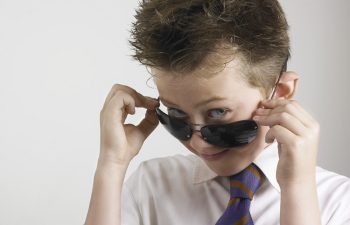 A 9 years old caucasian male youth. Smiling over a pair of dark sunglasses. Wearing white shirt and striped tie. White background.