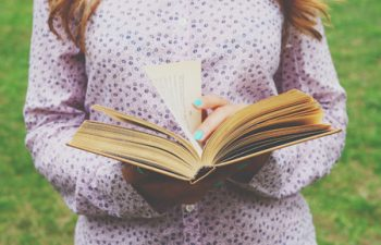 40227145 - young woman holding open book in her hands, summer background