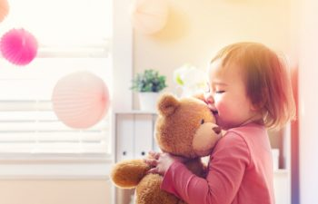 53023368 - happy toddler girl playing with her teddy bear at house