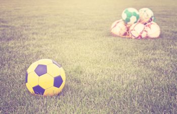 57912656 - retro filtered soccer balls on grass.