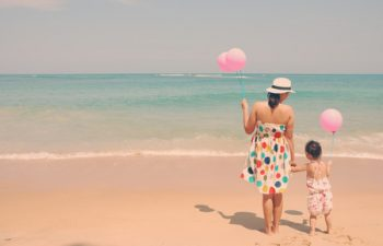 27882110 - retro style young mother and  her kid on the beach with pinky balloons