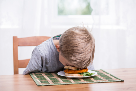 47721329 - boy falling asleep and landing face in food