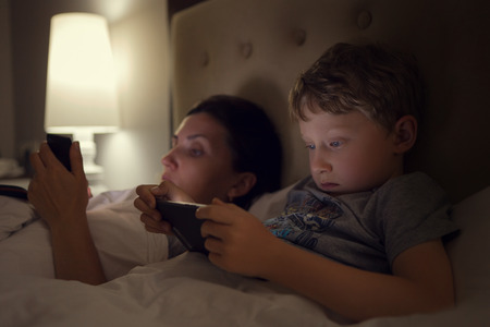 47115070 - mother with son lying in bed and look in their electronic device