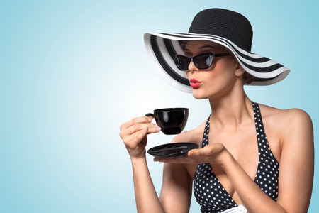 40479585 - a creative vintage photo of a beautiful pin-up girl drinking tea and showing good table manners.