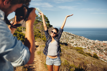 41018057 - happy young woman posing with her arms raised to her boyfriend taking her photos with digital camera. summer vacation fun, young couple hiking in countryside.