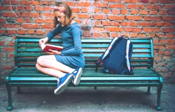 50840812 - a teenage girl is reading on a bench with brick wall in the background. toned image