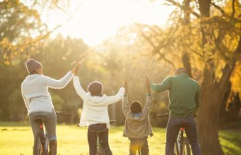 47297718 - rear view of a young family with arms raised on bike on an autumns day