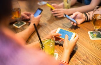 53070612 - leisure, technology, lifestyle and people concept - close up of hands with smartphones messaging at restaurant