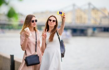 60303513 - happy tourist couple, two girlfriends traveling on holidays in europe smiling happy. caucasian women.