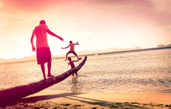 39662827 - father playing with sons at tropical beach with tilted horizon - concept of  family union with man and children having fun together - modified unrecognizable silhouettes - marsala filtered color tones