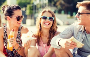 41729337 - friendship, leisure, summer and people concept - group of smiling friends in sunglasses sitting with food on city square