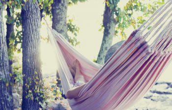 25794247 - person relaxing in a hammock in the shade of a tree on a hot summer day, view from behind. with retro filter effect.