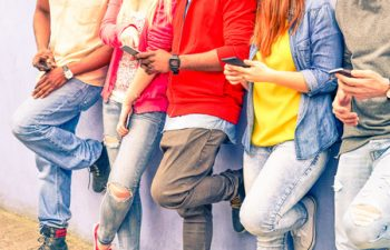 55465884 - multiracial group of friends texting sms and looking down to cell phone - interracial students hands using mobile - concept of young people addiction to web technology - focus on hand of red hair girl