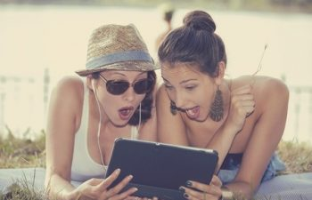 42706894 - closeup portrait two surprised girls looking at pad discussing latest gossip news. young shocked funny women friends reading sharing social media news on mobile pad computer outdoors in park