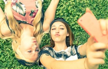38769438 - two pretty girls taking a self portrait - young women with a sportive casual outfit lying on meadow and having fun while taking a selfie