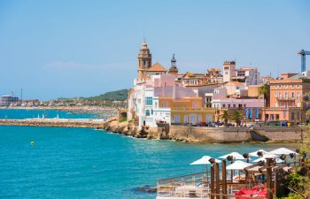 82425188 - sitges, catalunya, spain - june 20, 2017: view of the historical center and the ?hurch of sant bartomeu and santa tecla. copy space for text. isolated on blue background