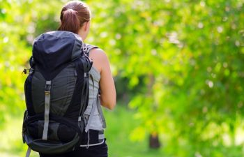 14244681 - young woman with backpack in a woods. hiking at summertime.