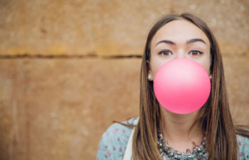 40327672 - closeup of beautiful young brunette teenage girl blowing pink bubble gum over a stone wall background