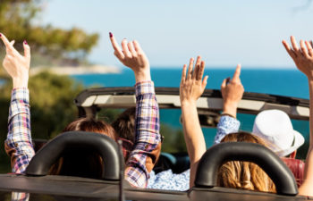 Group of happy young friends in cabriolet with raised hands driving on sunset.