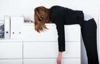 21260136 - side view of businesswoman sleeping on counter in office