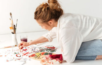 Image of concentrated young caucasian lady painter at workspace. Looking aside.