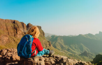 little girl with backpack hiking in mountains, family travel